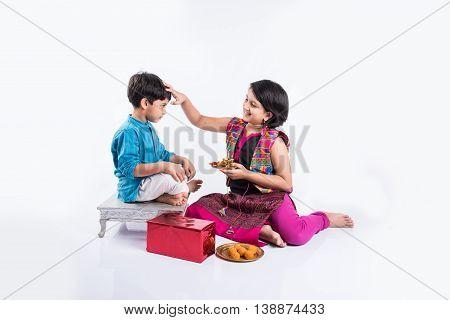 indian small brother and sister enjoying and celebrating Raksha Bandhan festival