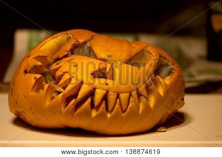 Rotted Pumpkin covered with mold face contorted remaining after the celebration of Halloween