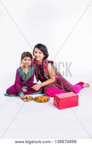 two cute indian small girls in traditional wear preparing pooja thali or puja thali
