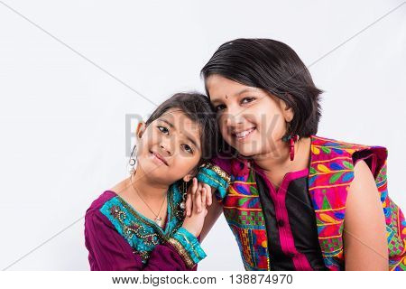 Closeup portrait of cute indian siblings in traditional wear, family looking at camera, isolated over white background