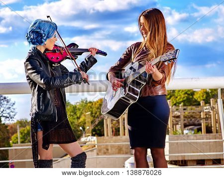 Music street performers two girls violinist with blue hair playing aganist sky with clouds outdoor. Violinist girls playing in city outdoor.
