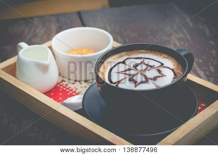 hot coffee with foam milk art. Black cup of coffee. Hot coffee in afternoon break. Coffee cup. coffee mocha on the wood desk. Coffee break.(selective focus vintage effect)