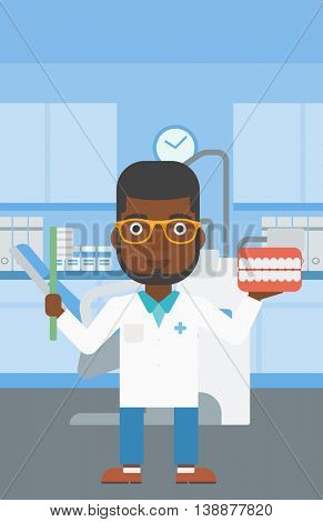 An african-american young male dentist holding dental jaw model and a toothbrush in doctor office. Vector flat design illustration. Vertical layout.