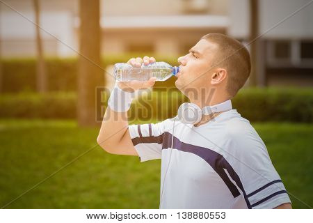 Portrait of thirsty sportsman drinking water from the plastic bottle in the park during the sunny day. Ideal for bottle pack shoot adding. Sport, fitness, nature and healthy lifestyle concepts.