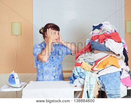 Young Caucasian Woman Ironed Clothes In The Room Near Window.