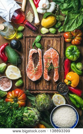 Dinner cooking ingredients. Two pieces of raw uncooked salmon fish with fresh vegetables, rice, herbs, lemon, spices and bottle of rose wine over rustic wooden board, top view, vertical composition
