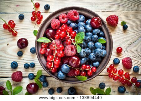 Fresh berries. Various summer berries in a bowl on rustic wooden table.