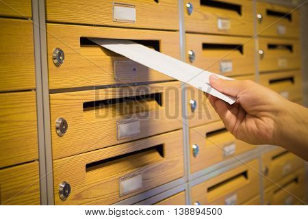 Mailman hand putting the yellow envelope into the gray mailbox