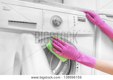Female hands in gloves washing washing machine. Close-up.
