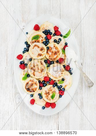 Syrniki or cottage cheese pancakes with fresh forest berries and sour cream sauce in serving dish over white wooden background, top view. Russian and Ukranian cuisine