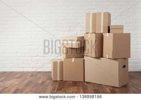 Moving in. Stack of cardboard boxes in the empty room with copy space