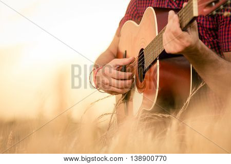 Close up of male hands playing acoustic guitar on the wheat field at the sunset. Retro, music, lifestyle concepts. poster