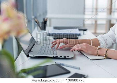 Close-up photo of female hands with accessories working on portable computer in a modern office, using keyboard