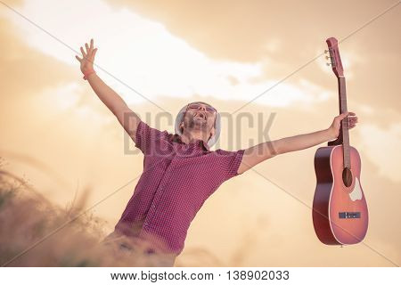 Cheerful music player holding acoustic guitar on wheat field. Sun and clouds in the background. Freedom, music, art and lifestyle concepts.