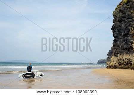 Ballybunion beach, county Kerry, Ireland - September 11, 2014: surfer standing with board on ballybunion beach in the wild atlantic way