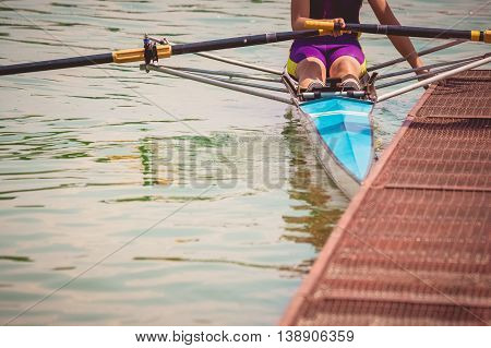 Rower in his boat preparing for the race next to the dock.