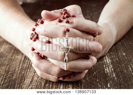 Praying hands holding red rosary with cross