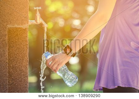 Close up of female hand wearing smart watch and pouring drinking water in plastic bottle on faucet in the park. Nature, summer. technology and healthy lifestyle concepts.