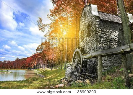 Old water mill on the lake in autumn.