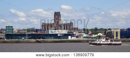 LIVERPOOL, ENGLAND, JULY 3. The Albert Docks from across the Mersey River on July 3, 2016, in Liverpool, England. Liverpool landmarks include the Ferry Exhibition Centre and Liverpool Cathedral.