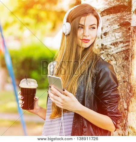 Cool teenage girl with smart phone, headphones and takeaway coffee. Beautiful young woman relaxing in park on sunny day. Vibrant colors, square format, medium retouch.
