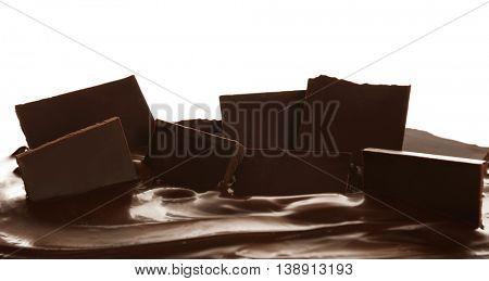 Melting pieces of dark chocolate bar on white background