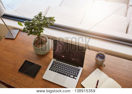 Top view shot of laptop computer digital tablet potted plant diary and a cup of coffee on wooden table. Modern work desk by a window.