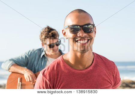Portrait of a smiling man wearing sunglasses in front of man playing guitar. African guy looking at camera during sunset. Portait of carefree black man in casual smiling.
