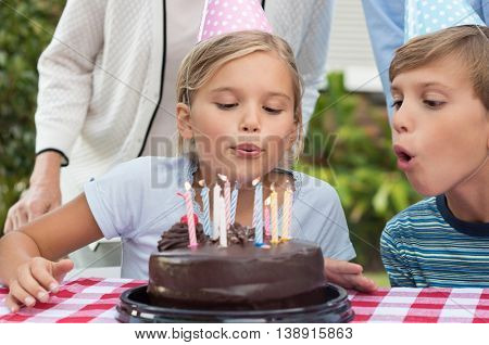 Young girl blowing out birthday candles of chocolate cake. Portrait of young girl celebrating birthday with family and brother. Brother helping sister blow candles on birthday cake.