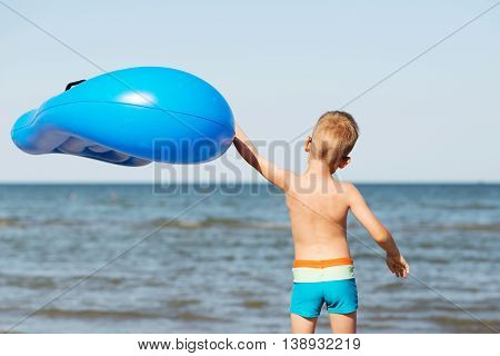 Little Kid Holding An Inflatable Mattress On The Beach On Hot Summer Day