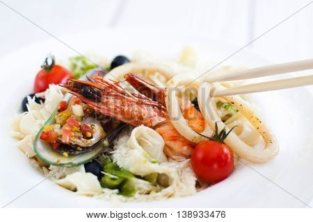 Asian seafood meal, chopsticks using for eating, closeup. Ingestion at chinese restaurant with traditional cutlery