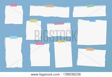 Pieces of ripped white ruled note paper are stuck with colorful sticky tapes on blue background.