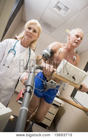 Doctor Monitoring The Heart-Rate Of Patient On A Treadmill
