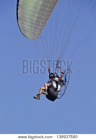man flying on a parachute blue sky background poster