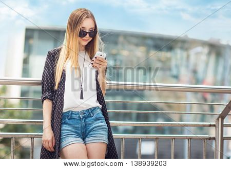 Trendy young gilr looking their smartphone outdoors. Close-up trendy woman in a warmly day