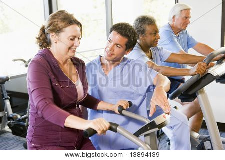 Nurse With Patient In Rehabilitation Using Exercise Machine