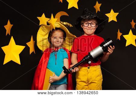 Cute kids, five years old boy and girl, playing sky watchers with a telescope standing among handmade stars and moon