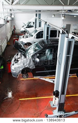 Engine installing conveyor, car engineering. Line of new minibuses with raised hood ready for motor installation automobile production concept