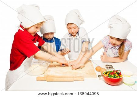 Happy kids in baker's uniform making homemade cookies with cookie cutters, isolated on white