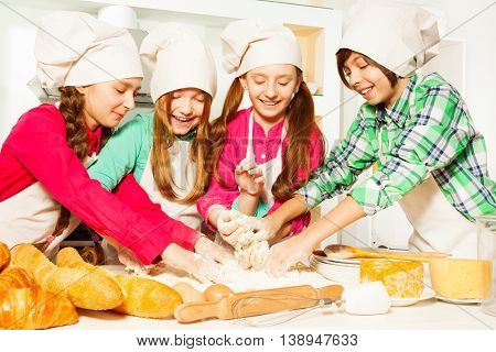 Four young bakers, kids in cook's uniform,  kneading dough in the kitchen