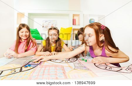 Ten years old girl making her move, playing the tabletop game with her friends at the playroom