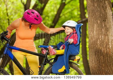 Smiling toddler girl in bicycle child seat and protection helmet smiling and mother talking to daughter