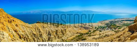 The mountains of Judean desert overlook the Dead Sea and its coastline with green palms of the local kibbutz Ein Gedi Israel.