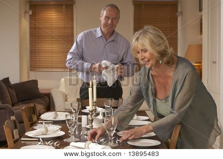 Couple Preparing Table For A Dinner Party