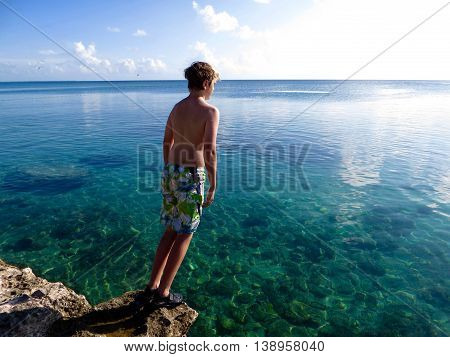 Young boy standing on a rock with his back to the camera high above the Caribbean ocean about to dive into the clear turquoise water below