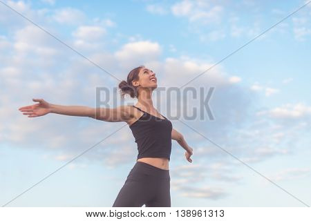 woman enjoying sunset with arms outspread and face raised in sky.