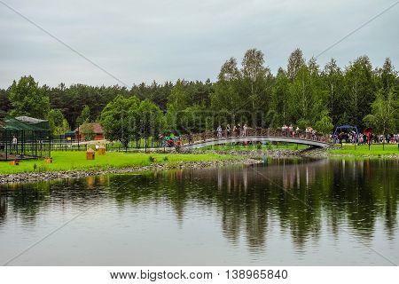 RUSSIA, BELGOROD - June 13 2016: New Belgorod zoo in the woods. Walkup and the bridge across the pond.
