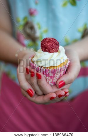 Woman In Floral Dress With Painted Nails Holding Decorated Cupcake