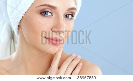 Beautiful woman with a towel on her head on a gray background.