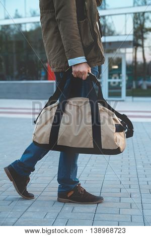 A man with a bag in his hand goes past the airport building. Close-up